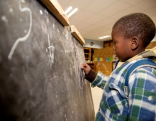Young boy using the blackboard
