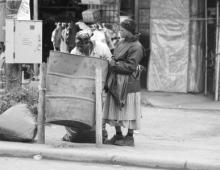 Women next to a rubbish drum