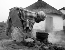 Old lady cooks on the fire
